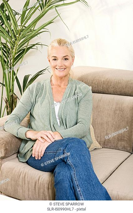 Mature woman sitting on sofa