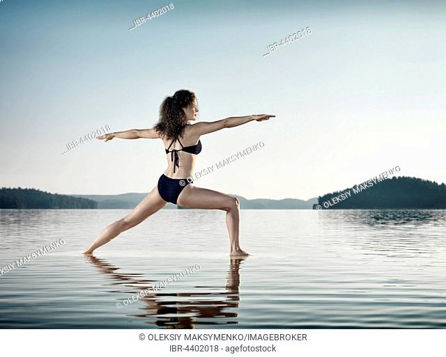 Young woman practicing Hatha yoga on a floating platform in water on the lake in morning light, Yoga Warrior posture, Dandayamana Dhanurasana