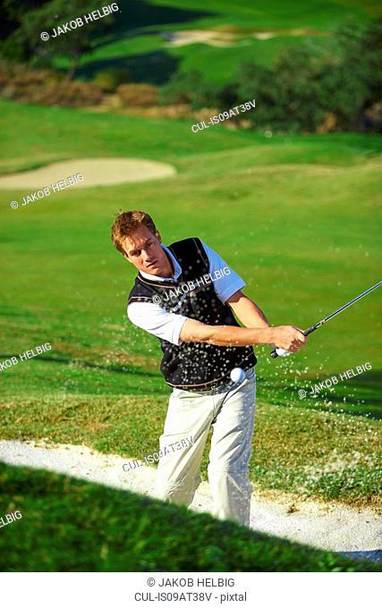 Golfer taking golf swing in sand trap, golf ball in mid air