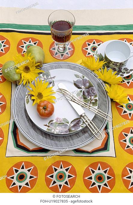 Close-up of patterned yellow cloth and grey crockery