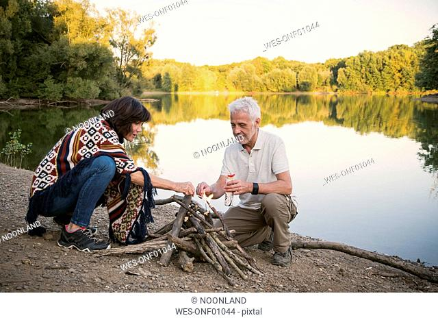 Senior couple lighting a campfire at a lake in the evening