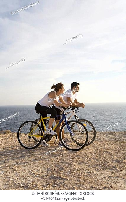 Couple enjoying the views in a cliff with their bikes