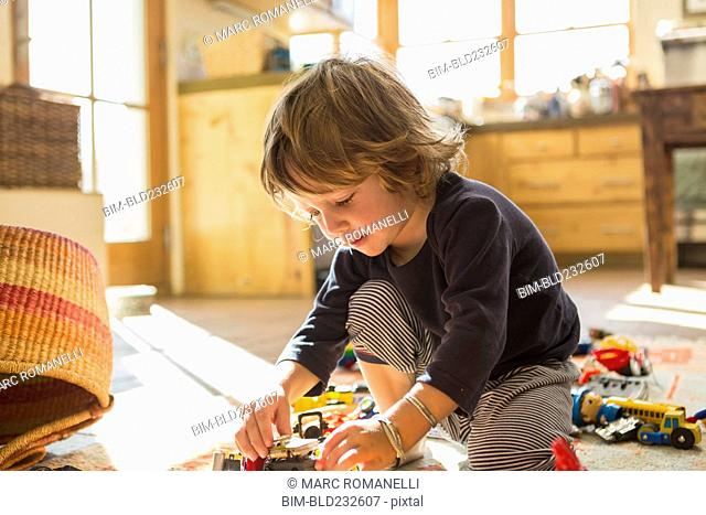 Caucasian boy playing with toys on floor