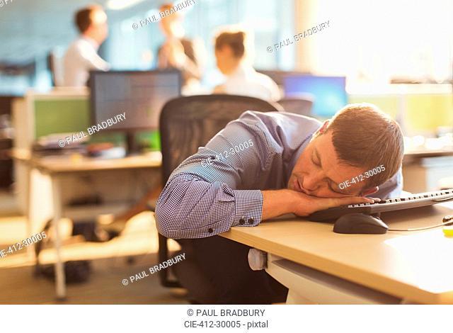 Businessman sleeping on desk in office