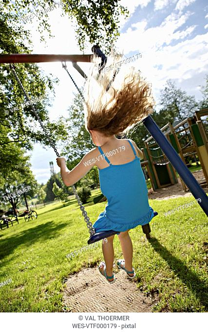 Germany, Coburg, teenage girl on a swing in the park