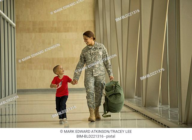 African American soldier and son walking in airport