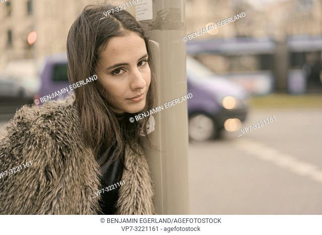 woman leaning head on street lamppost in city, next to car traffic, in Munich, Germany