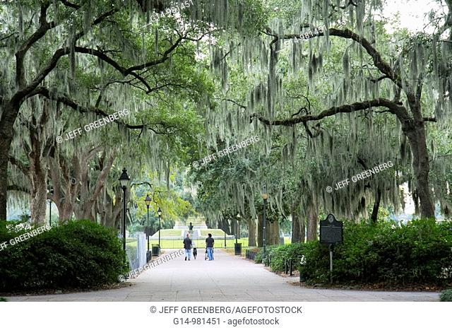 Georgia, Savannah, South, Savannah Historic District, National Historic Landmark, Forsyth Park, shaded pathway, moss draped tree, man, woman, dog, family