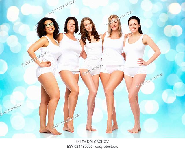 friendship, beauty, body positive and people concept - group of happy women different in white underwear over blue holidays lights background