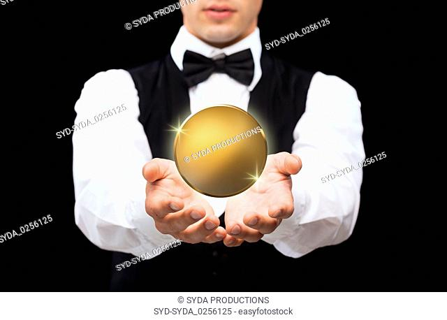 close up of magician with golden coin over black