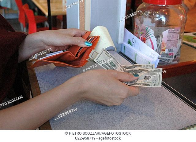 New York City (USA): a woman paying a bill in dollars