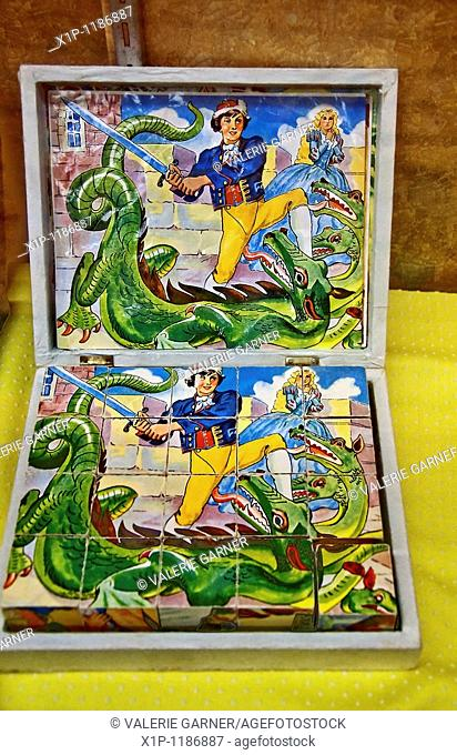 This image shows an antique boy pirate and dragon block puzzle in a display case Vertical shot with yellow polka dot fabric in this nostalgia object