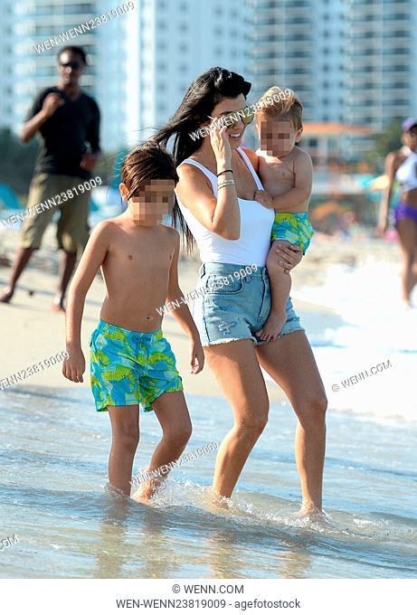 Kourtney Kardashian wears a white one piece swimsuit and denim hotpants as she takes her kids to the beach in Miami Featuring: Kourtney Kardashian, Mason Disick