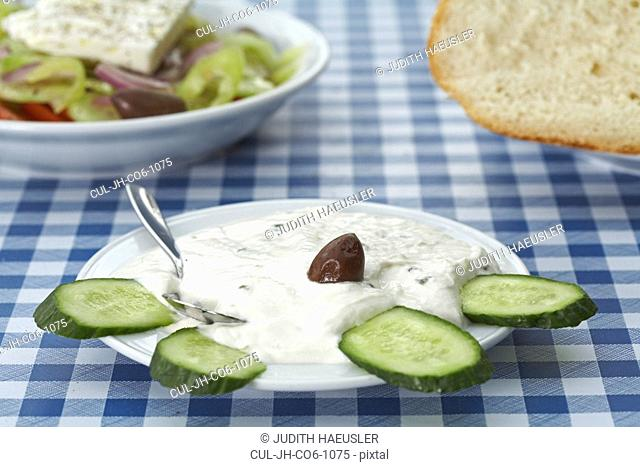 Greek tsatsiki salad decorated with cucumber on table Greek salad and bread in background