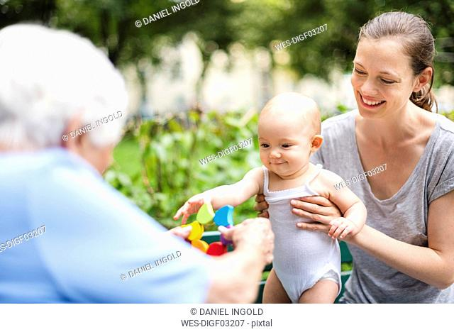 Portrait of smiling baby girl with grandmother and mother in a park