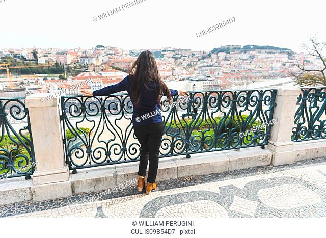 Rear view of woman looking away at elevated view of Lisbon, Portugal