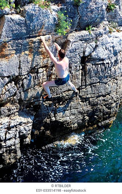 climber is climbing up on cliffs over the ocean