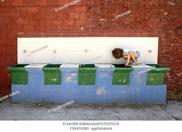 5 year old girl drinking at washing place
