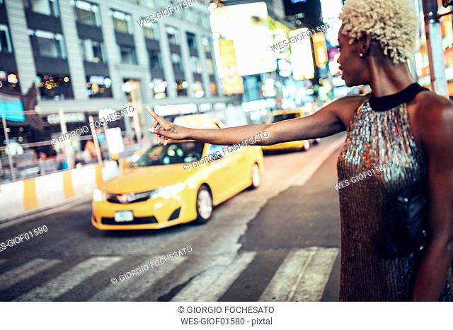 USA, New York City, young woman hailing a taxi on Times Square at night