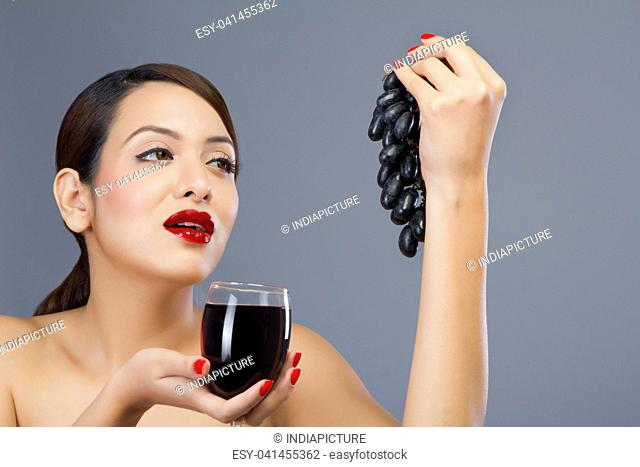 Woman holding a glass of wine and grapes
