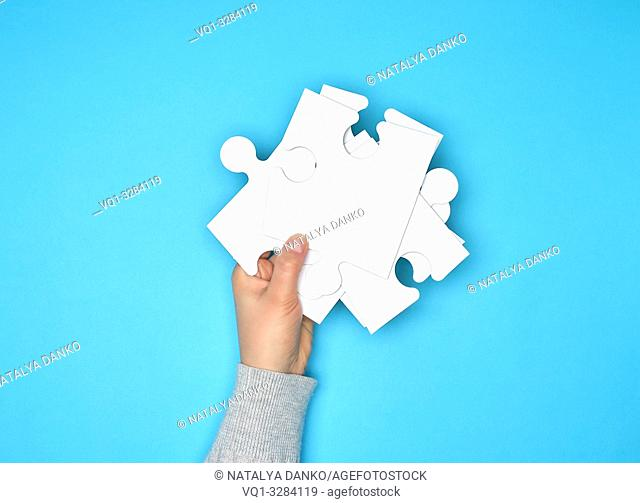 female hand holding a stack of large white paper puzzles on a blue background