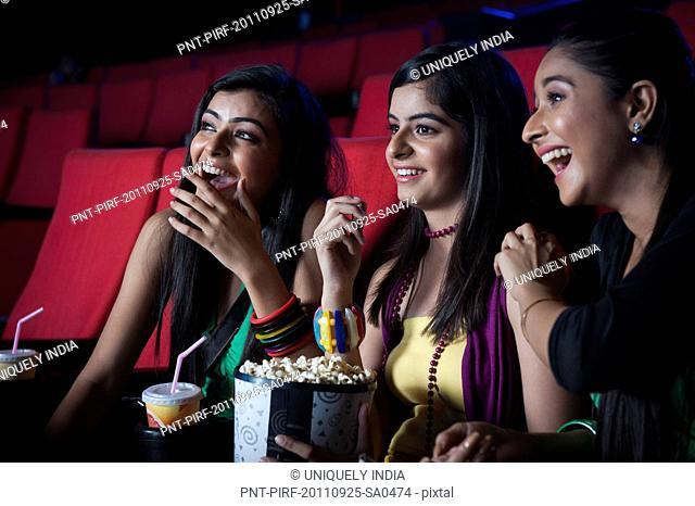 Three female friends enjoying movie with popcorns in a cinema hall