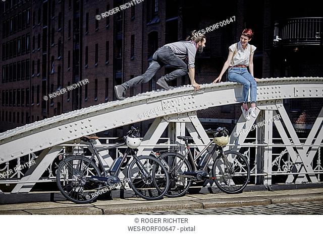 Germany, Hamburg, couple with electric bicycles having fun on a bridge
