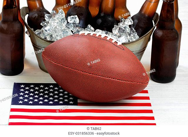 Close up of American football, ice cold beer in bucket, and flag with rustic white wood underneath. Perfect for the Fourth of July holiday