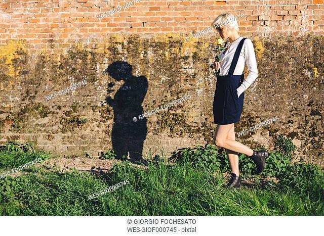 Blond woman with rose walking along a brick wall