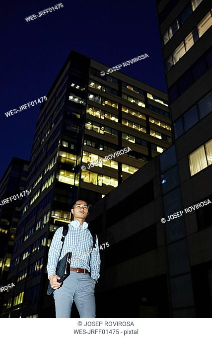 Businessman with folder and headphones walking in the city at night