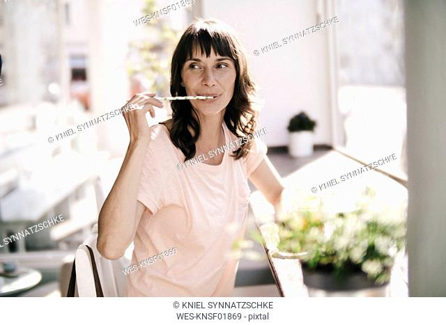 Woman sitting cafe, licking a drinking straw