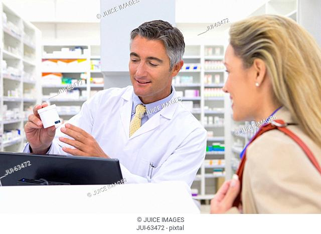 Pharmacist showing customer medication from behind pharmacy counter