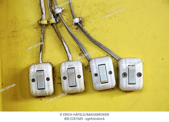 Four light switches on a yellow wall, Sihanoukeville, Cambodia, Asia