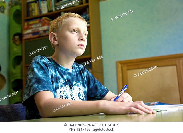 Serious Teenage Boy Sitting at Home Desk and Learning