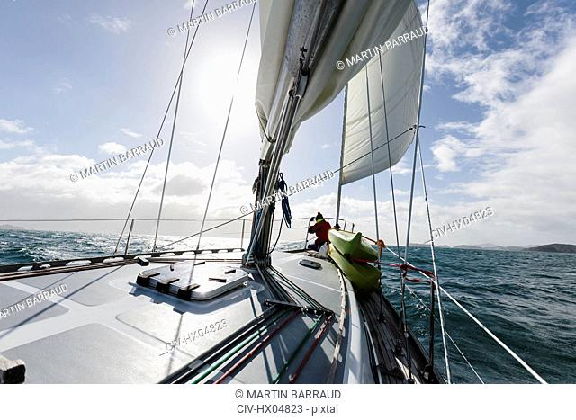 Woman at bow of sailboat on sunny ocean, Vava'u, Tonga, Pacific Ocean