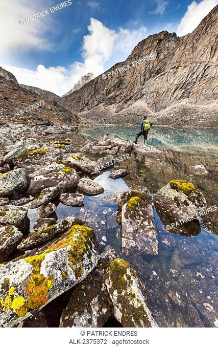 Day hiker alongside a clear mountain lake in the Arrigetch Peaks, Gates of the Arctic National Park, Alaska