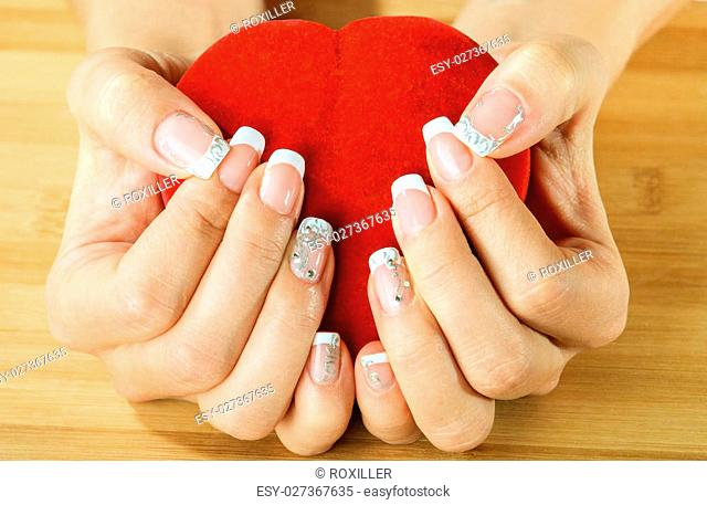 beautiful female hands with manicure holding a box of heart-shaped