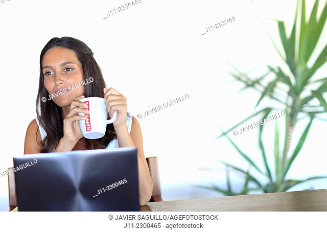 Woman working with laptop, holding mug