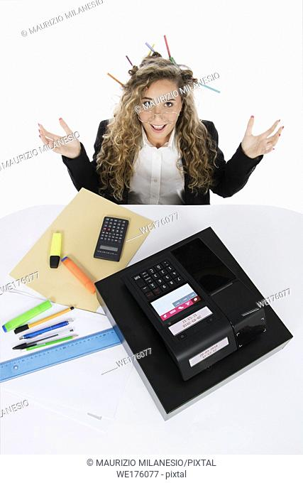 Shocked bookkeeper with open arms and pencils in her hair seen from above, in front of her a cash register, highlighters and pens scattered on the desk near a...