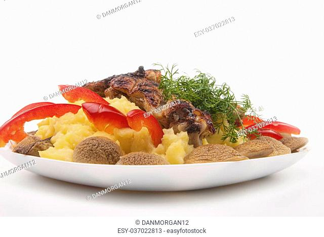 plate with grilled fresh meat and mash potato, mashrooms and vegatables, against white background