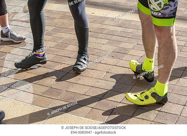 A partial view of 3 bike riders' legs standing on a sidewalk wearing special clothing and shoes
