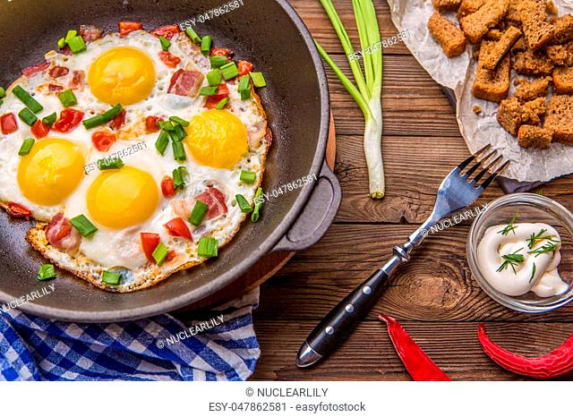 Fred eggs in pan with tomatoes and green fresh onion. Breakfast. Healthy food