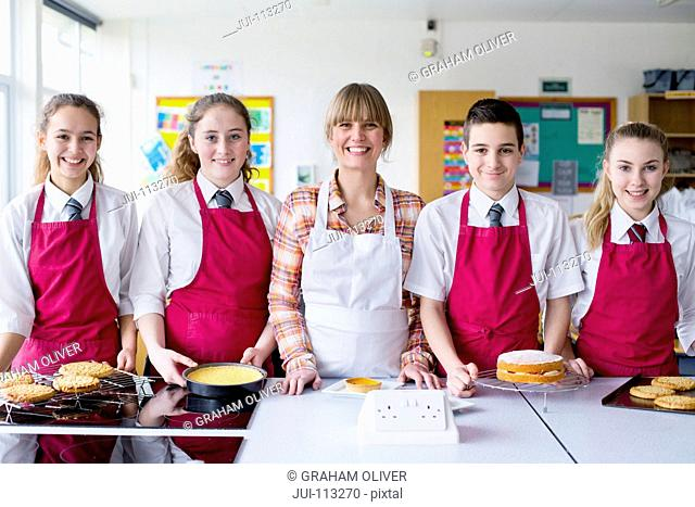 Portrait confident home economics teacher and students with desserts in kitchen classroom