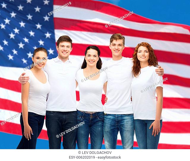 advertising, friendship, patriotism and people concept - group of smiling teenagers in white blank t-shirts over american flag background