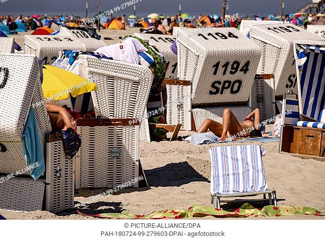 24 July 2018, Germany, Sankt Peter Ording: Beach guests sunbathe between beach chairs. Photo: Axel Heimken/dpa. - Sankt Peter-Ording/Schleswig-Holstein/Germany