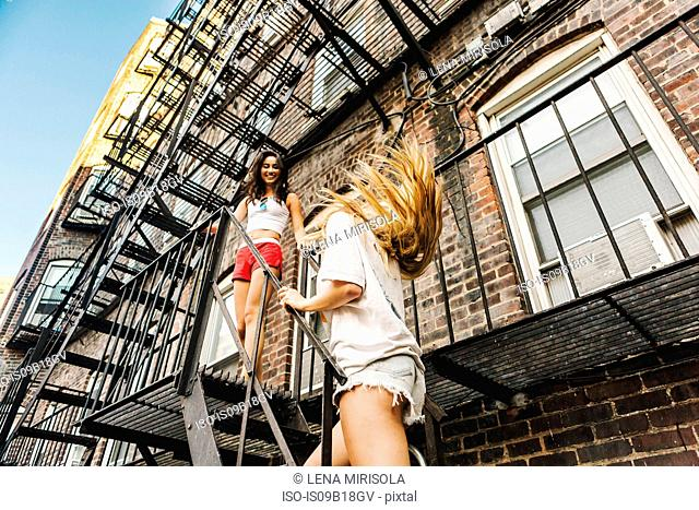 Women climbing fire escape ladder of apartment building, Boston, MA, USA