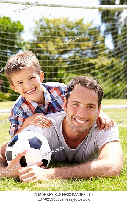 Portrait Of Father And Son With Football