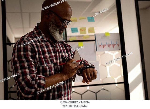 Senior graphic designer using smartwatch