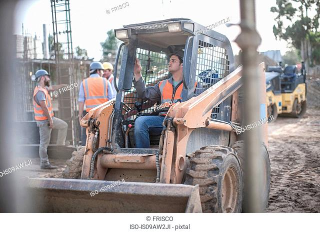 Construction worker driving excavator on construction site