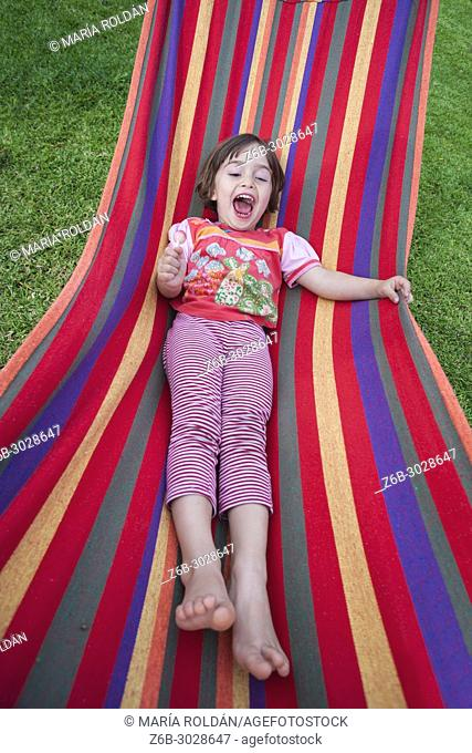 littlegirl having fun in a colourful hammock